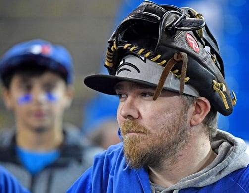 Mar 28, 2019; Toronto, Ontario, CAN; A Toronto Blue Jays fan wears a glove on his head as he watches batting practice before the home opener against Detroit Tigers at Rogers Centre. Mandatory Credit: Dan Hamilton-USA TODAY Sports