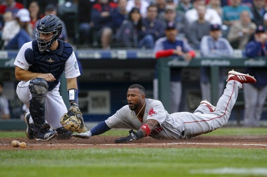 Mar 28, 2019; Seattle, WA, USA; Boston Red Sox third baseman Eduardo Nunez (right) scores a run as Seattle Mariners catcher David Freitas (left) watches an errant throw during the second inning at T-Mobile Park. Mandatory Credit: Joe Nicholson-USA TODAY Sports