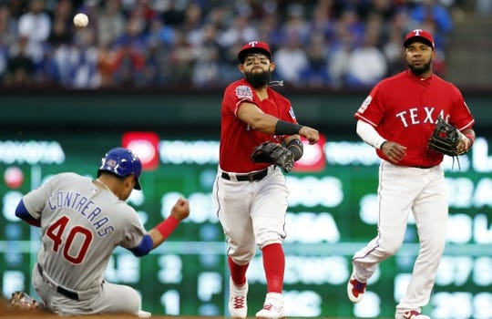Mar 30, 2019; Arlington, TX, USA; Texas Rangers second baseman Rougned Odor (12) throws to first forcing out Chicago Cubs catcher Willson Contreras (40) on the first half of a double play as shortstop Elvis Andrus, right, watches during the first inning in a baseball game at Globe Life Park in Arlington. Mandatory Credit: Jim Cowsert-USA TODAY Sports