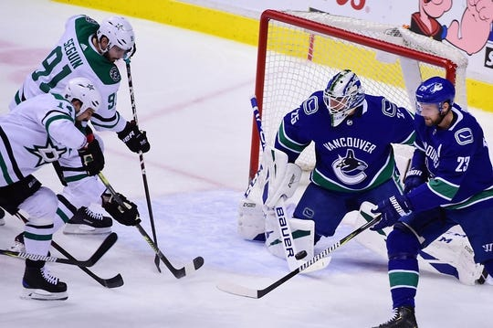Mar 30, 2019; Vancouver, British Columbia, CAN; Dallas Stars forward Jamie Benn (14) and forward Tyler Sequin (91) shoot the puck against Vancouver Canucks goaltender Jacob Markstrom (25) and defenseman Alexander Edler (23) during the first period at Rogers Arena. Mandatory Credit: Anne-Marie Sorvin-USA TODAY Sports