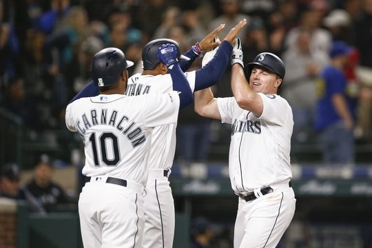 Mar 30, 2019; Seattle, WA, USA; Seattle Mariners first baseman Jay Bruce (32) is greeted by designated hitter Edwin Encarnacion (10) and left fielder Domingo Santana (16) after hitting a three-run home run against the Boston Red Sox during the fifth inning at T-Mobile Park. Mandatory Credit: Joe Nicholson-USA TODAY Sports
