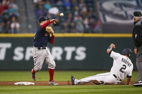 Mar 30, 2019; Seattle, WA, USA; Boston Red Sox second baseman Brock Holt (12) turns a double play against the Seattle Mariners during the fourth inning at T-Mobile Park. Mandatory Credit: Joe Nicholson-USA TODAY Sports
