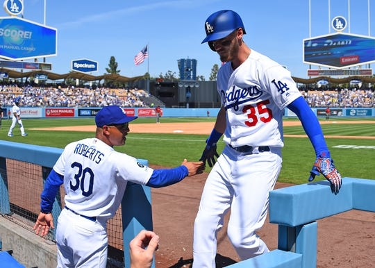 Mar 31, 2019; Los Angeles, CA, USA; Los Angeles Dodgers center fielder Cody Bellinger (35) is greeted in the dugout by manager Dave Roberts (30) after hitting a solo home run in the third inning against the Arizona Diamondbacks at Dodger Stadium. Mandatory Credit: Jayne Kamin-Oncea-USA TODAY Sports