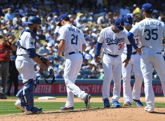 Mar 31, 2019; Los Angeles, CA, USA; Los Angeles Dodgers catcher Russell Martin (55) and left fielder Chris Taylor (3) and center fielder Cody Bellinger (35) look on as manager Dave Roberts (30) pulls starting pitcher Walker Buehler (21) in the fourth inning against the Arizona Diamondbacks at Dodger Stadium. Mandatory Credit: Jayne Kamin-Oncea-USA TODAY Sports