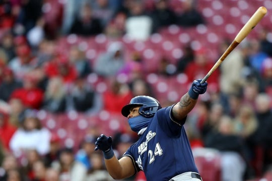 Apr 1, 2019; Cincinnati, OH, USA; Milwaukee Brewers first baseman Jesus Aguilar (24) hits a two RBI single against the Cincinnati Reds in the first inning at Great American Ball Park. Mandatory Credit: Aaron Doster-USA TODAY Sports