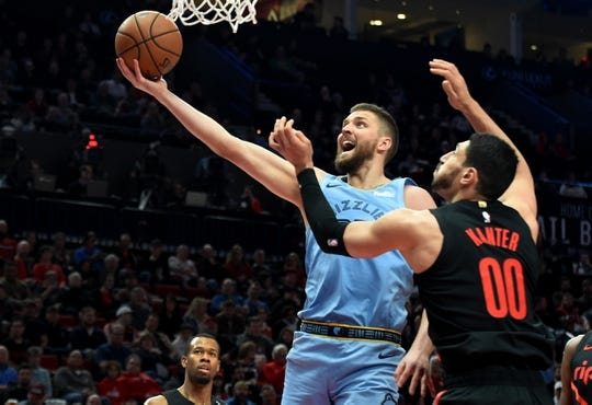 Apr 3, 2019; Portland, OR, USA; \Memphis Grizzlies forward Chandler Parsons (25) drives to the basket on Portland Trail Blazers center Enes Kanter (00) during the first half of the game at the Moda Center. Mandatory Credit: Steve Dykes-USA TODAY Sports