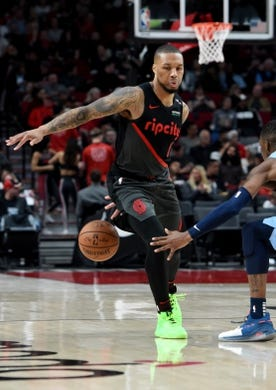 Apr 3, 2019; Portland, OR, USA; Portland Trail Blazers guard Damian Lillard (0) dribbles behind his back to get past Memphis Grizzlies guard Delon Wright (2) during the second half of the game at the Moda Center. The Blazers won 116-89. Mandatory Credit: Steve Dykes-USA TODAY Sports
