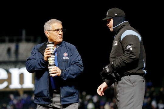 Apr 10, 2019; Chicago, IL, USA; Ken Corso of baseball operations at the Chicago Cubs collects cups after giving the infield umpires hot chocolate between innings of the game between the Chicago Cubs and the Pittsburgh Pirates at Wrigley Field. Mandatory Credit: Jon Durr-USA TODAY Sports