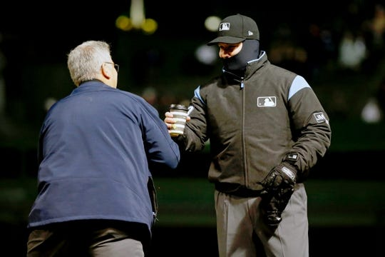 Apr 10, 2019; Chicago, IL, USA; (Editors note: captio correction) Ken Corso of ballpark operations for the Chicago Cubs gives first base umpire Mike Estabrook (83) a cup of hot chocolate between innings of the game between the Chicago Cubs and the Pittsburgh Pirates at Wrigley Field. Mandatory Credit: Jon Durr-USA TODAY Sports