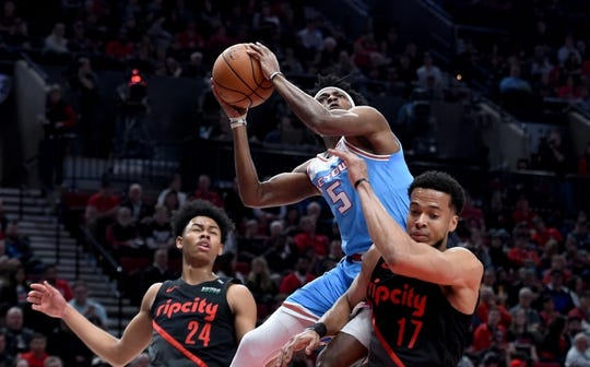 Apr 10, 2019; Portland, OR, USA; Sacramento Kings guard De'Aaron Fox (5) shoots the ball between Portland Trail Blazers guard Anfernee Simons (24) and forward Skal Labissiere (17) during the first half of the game at the Moda Center. Mandatory Credit: Steve Dykes-USA TODAY Sports