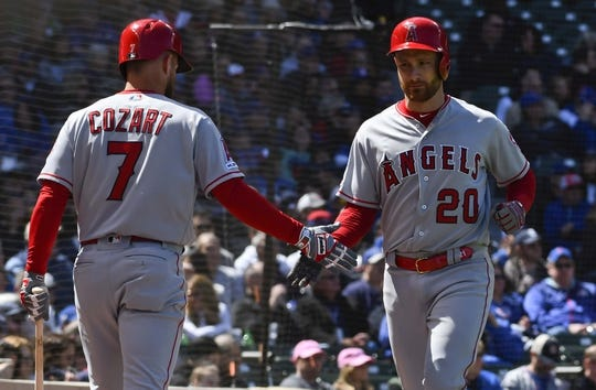 Apr 13, 2019; Chicago, IL, USA; Los Angeles Angels catcher Jonathan Lucroy (20) high fives Los Angeles Angels third baseman Zack Cozart (7) after scoring against the Chicago Cubs in the second inning at Wrigley Field. Mandatory Credit: Matt Marton-USA TODAY Sports
