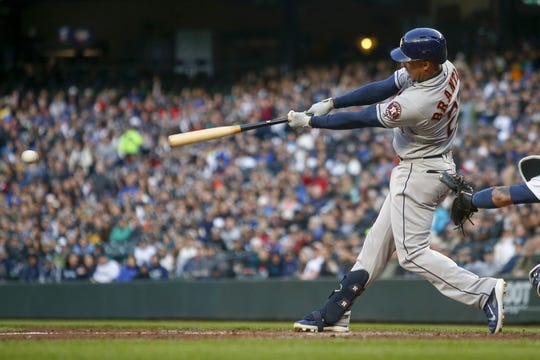 Apr 13, 2019; Seattle, WA, USA; Houston Astros left fielder Michael Brantley (23) hits an RBI-single against the Seattle Mariners during the third inning at T-Mobile Park. Mandatory Credit: Joe Nicholson-USA TODAY Sports