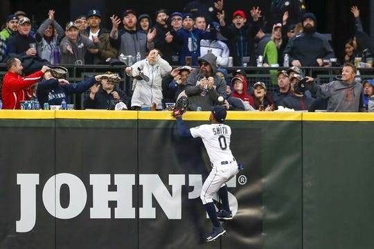 Apr 13, 2019; Seattle, WA, USA; Seattle Mariners center fielder Mallex Smith (0) and fans fail to catch a home run by the Houston Astros during the fifth inning at T-Mobile Park. Mandatory Credit: Joe Nicholson-USA TODAY Sports