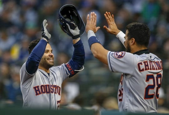 Apr 13, 2019; Seattle, WA, USA; Houston Astros second baseman Jose Altuve (27) is greeted outside the dugout by catcher Robinson Chirinos (28) after hitting a solo-home run against the Seattle Mariners during the fifth inning at T-Mobile Park. Mandatory Credit: Joe Nicholson-USA TODAY Sports