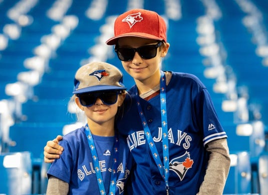 Apr 14, 2019; Toronto, Ontario, CAN; Young fans pose before the start of an MLB game between the Tampa Bay Rays and Toronto Blue Jays at Rogers Centre. Mandatory Credit: Kevin Sousa-USA TODAY Sports