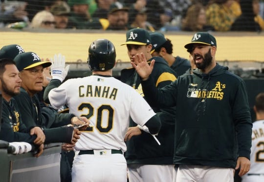 Apr 17, 2019; Oakland, CA, USA; Oakland Athletics first baseman Mark Canha (20) high fives teammates after scoring a run against the Houston Astros during the second inning at Oakland Coliseum. Mandatory Credit: Kelley L Cox-USA TODAY Sports