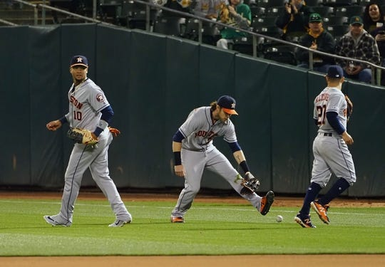 Apr 17, 2019; Oakland, CA, USA; Houston Astros right fielder Josh Reddick (22) gathers the ball between first baseman Yuli Gurriel (10) and second baseman Jose Altuve (27) during the fifth inning against the Oakland Athletics at Oakland Coliseum. Mandatory Credit: Kelley L Cox-USA TODAY Sports