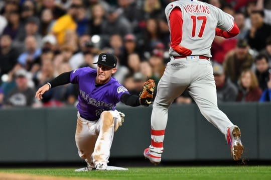 Apr 18, 2019; Denver, CO, USA; Colorado Rockies first baseman Ryan McMahon (24) fields a ball as Philadelphia Phillies left fielder Rhys Hoskins (17) reaches the bag in the fourth inning at Coors Field. Mandatory Credit: Ron Chenoy-USA TODAY Sports