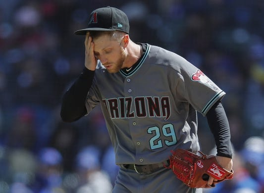 Apr 19, 2019; Chicago, IL, USA; Arizona Diamondbacks starting pitcher Merrill Kelly (29) reacts after giving up a walk to the Chicago Cubs during the first inning at Wrigley Field. Mandatory Credit: Jim Young-USA TODAY Sports