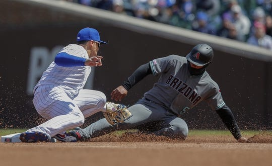 Apr 19, 2019; Chicago, IL, USA; Arizona Diamondbacks third baseman Eduardo Escobar (5) is tagged out by Chicago Cubs shortstop Javier Baez (9) trying to steal second base during the first inning at Wrigley Field. Mandatory Credit: Jim Young-USA TODAY Sports