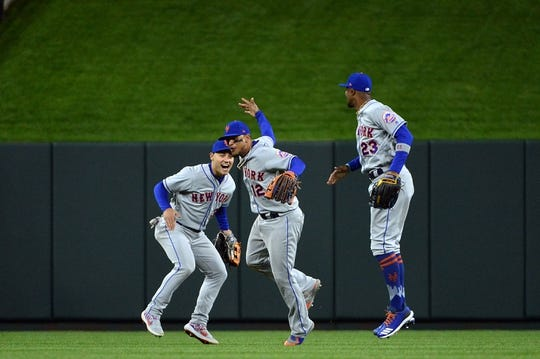 Apr 19, 2019; St. Louis, MO, USA; New York Mets right fielder Michael Conforto (30) and center fielder Juan Lagares (12) and left fielder Keon Broxton (23) celebrate after defeating the St. Louis Cardinals at Busch Stadium. Mandatory Credit: Jeff Curry-USA TODAY Sports