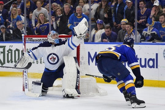 Apr 20, 2019; St. Louis, MO, USA; Winnipeg Jets goaltender Connor Hellebuyck (37) makes a save against St. Louis Blues center Robby Fabbri (15) during the first period in game six of the first round of the 2019 Stanley Cup Playoffs at Enterprise Center. Mandatory Credit: Jeff Curry-USA TODAY Sports