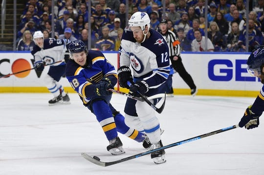 Apr 20, 2019; St. Louis, MO, USA; Winnipeg Jets right wing Kevin Hayes (12) tries to move the puck up ice as St. Louis Blues center Robert Thomas (18) and left wing Pat Maroon (7) defend during the first period in game six of the first round of the 2019 Stanley Cup Playoffs at Enterprise Center. Mandatory Credit: Jeff Curry-USA TODAY Sports