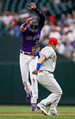 Apr 20, 2019; Denver, CO, USA; Philadelphia Phillies second baseman Cesar Hernandez (16) tags out Colorado Rockies center fielder David Dahl (26) in a run down in the first inning at Coors Field. Mandatory Credit: Isaiah J. Downing-USA TODAY Sports