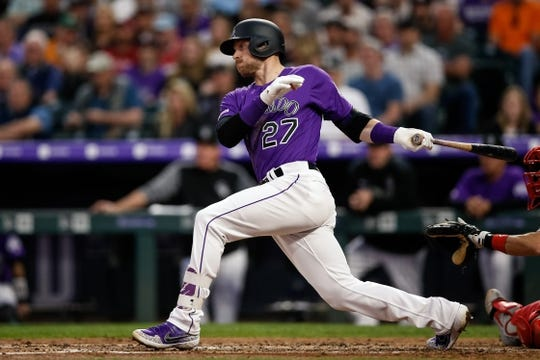 Apr 20, 2019; Denver, CO, USA; Colorado Rockies shortstop Trevor Story (27) hits an RBI single in the third inning against the Philadelphia Phillies at Coors Field. Mandatory Credit: Isaiah J. Downing-USA TODAY Sports
