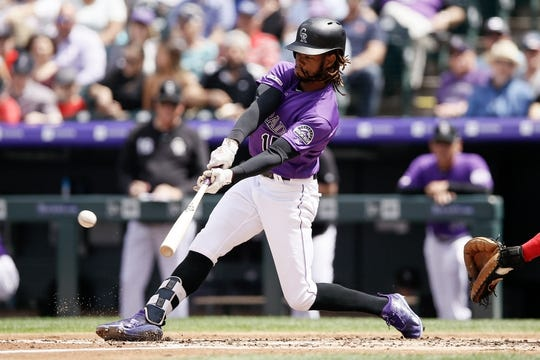 Apr 24, 2019; Denver, CO, USA; Colorado Rockies left fielder Raimel Tapia (15) hits a double in the second inning against the Washington Nationals at Coors Field. Mandatory Credit: Isaiah J. Downing-USA TODAY Sports