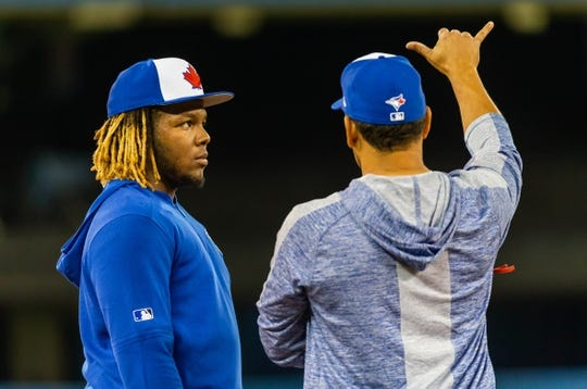 Apr 26, 2019; Toronto, Ontario, CAN; Vladimir Guerrero Jr. takes instructions from third base coach Luis Rivera before playing the Oakland Athletics at the Rogers Centre. Mandatory Credit: Kevin Sousa-USA TODAY Sports