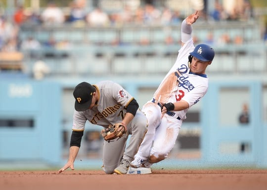 April 27, 2019; Los Angeles, CA, USA; Los Angeles Dodgers left fielder Joc Pederson (31) is out at second against Pittsburgh Pirates second baseman Adam Frazier (26) during the first inning at Dodger Stadium. Mandatory Credit: Gary A. Vasquez-USA TODAY Sports