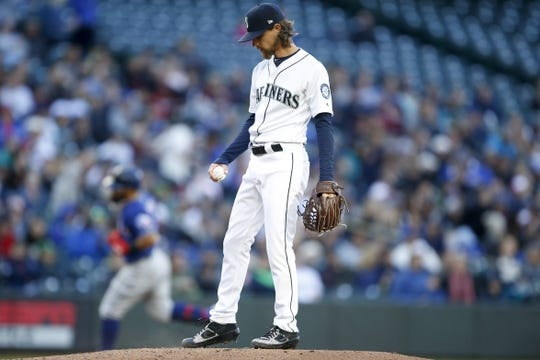 Apr 27, 2019; Seattle, WA, USA; Seattle Mariners starting pitcher Mike Leake (8) reacts after giving up a three-run home run to Texas Rangers second baseman Rougned Odor (background) during the second inning at T-Mobile Park. Mandatory Credit: Jennifer Buchanan-USA TODAY Sports