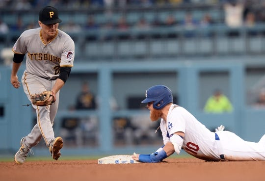 April 27, 2019; Los Angeles, CA, USA; Los Angeles Dodgers third baseman Justin Turner (10) reaches second ahead of Pittsburgh Pirates second baseman Adam Frazier (26) during the fourth inning at Dodger Stadium. Mandatory Credit: Gary A. Vasquez-USA TODAY Sports