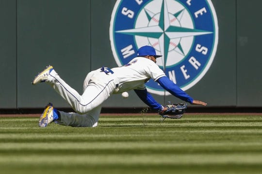 Apr 28, 2019; Seattle, WA, USA; Seattle Mariners right fielder Domingo Santana (16) fails to catch a line drive against the Texas Rangers during the fifth inning at T-Mobile Park. Mandatory Credit: Joe Nicholson-USA TODAY Sports