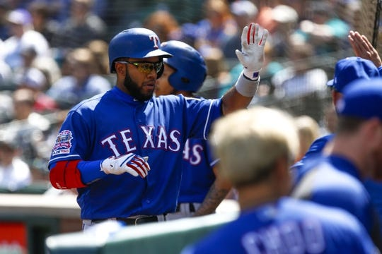 Apr 28, 2019; Seattle, WA, USA; Texas Rangers shortstop Elvis Andrus (1) is greeted outside the dugout after hitting a two-run home run against the Seattle Mariners during the third inning at T-Mobile Park. Mandatory Credit: Joe Nicholson-USA TODAY Sports
