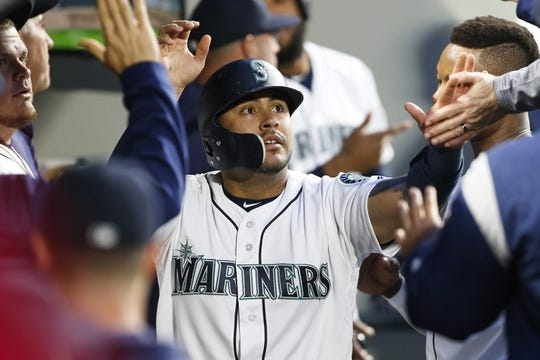Apr 30, 2019; Seattle, WA, USA; Seattle Mariners catcher Omar Narvaez (22) exchanges high-fives in the dugout after scoring a run against the Chicago Cubs during the fourth inning at T-Mobile Park. Mandatory Credit: Joe Nicholson-USA TODAY Sports