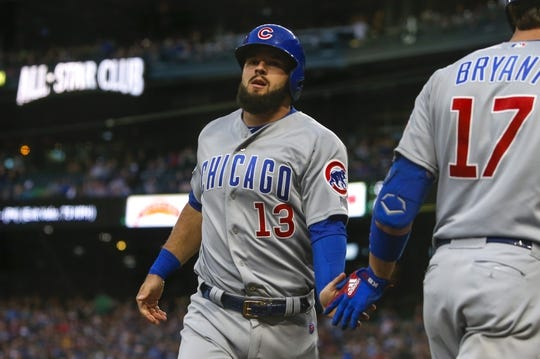 Apr 30, 2019; Seattle, WA, USA; Chicago Cubs third baseman David Bote (13) is greeted outside the dugout after scoring a run against the Seattle Mariners during the fourth inning at T-Mobile Park. Mandatory Credit: Joe Nicholson-USA TODAY Sports
