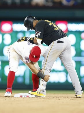 Apr 30, 2019; Arlington, TX, USA;Pittsburgh Pirates catcher Elias Diaz (32) is grabbed by Texas Rangers second baseman Rougned Odor (12) after hitting a double in the fourth inning at Globe Life Park in Arlington. Mandatory Credit: Tim Heitman-USA TODAY Sports