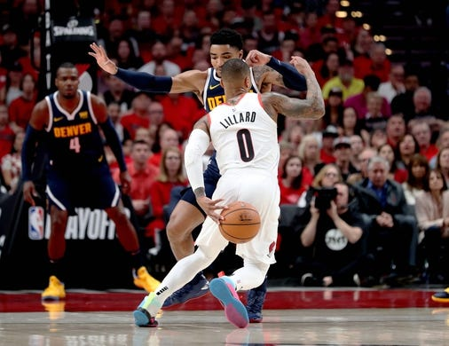 May 5, 2019; Portland, OR, USA; Portland Trail Blazers guard Damian Lillard (0) changes direction as he dribbles against Denver Nuggets guard Gary Harris (14) in the first half of game four of the second round of the 2019 NBA Playoffs at Moda Center. Mandatory Credit: Jaime Valdez-USA TODAY Sports