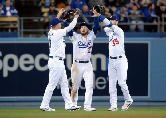May 10, 2019; Los Angeles, CA, USA; Los Angeles Dodgers left fielder Joc Pederson (31) center fielder Alex Verdugo (27) and right fielder Cody Bellinger (35) celebrate the 5-0 victory against the Washington Nationals at Dodger Stadium. Mandatory Credit: Gary A. Vasquez-USA TODAY Sports