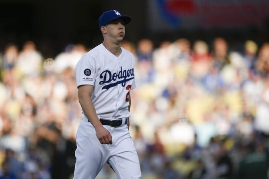 May 11, 2019; Los Angeles, CA, USA; Los Angeles Dodgers starting pitcher Walker Buehler (21) reacts while walking off the field to end the top of the first inning against the Washington Nationals at Dodger Stadium. Mandatory Credit: Kelvin Kuo-USA TODAY Sports