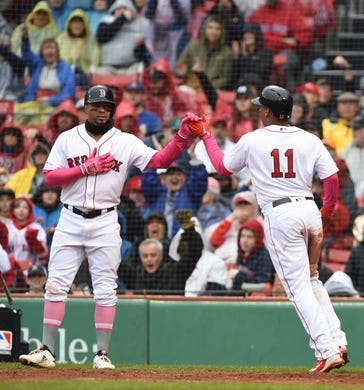 May 12, 2019; Boston, MA, USA; Boston Red Sox shortstop Xander Bogaerts (2) high fives third baseman Rafael Devers (11) after scoring during the fifth inning against the Seattle Mariners at Fenway Park. Mandatory Credit: Bob DeChiara-USA TODAY Sports
