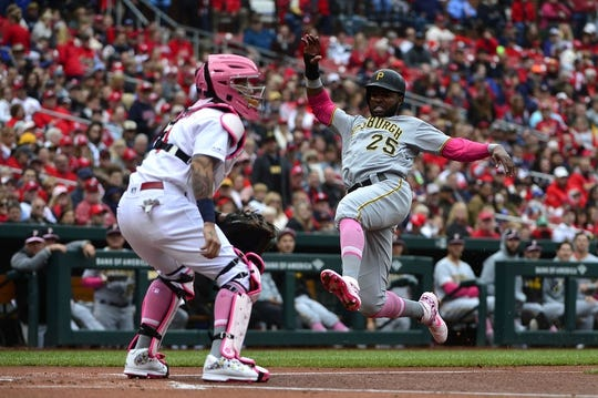 May 12, 2019; St. Louis, MO, USA; Pittsburgh Pirates right fielder Gregory Polanco (25) leaps to slide in at home as St. Louis Cardinals catcher Yadier Molina (4) waits for the the throw during the first inning at Busch Stadium. Mandatory Credit: Jeff Curry-USA TODAY Sports