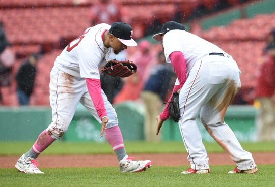 May 12, 2019; Boston, MA, USA; Boston Red Sox right fielder Mookie Betts (50) gives third baseman Rafael Devers (11) a low five after defeating the Seattle Mariners at Fenway Park. Mandatory Credit: Bob DeChiara-USA TODAY Sports