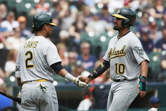 May 19, 2019; Detroit, MI, USA; Oakland Athletics shortstop Marcus Semien (10) is congratulated by designated hitter Khris Davis (2) after scoring in the third inning against the Detroit Tigers at Comerica Park. Mandatory Credit: Rick Osentoski-USA TODAY Sports