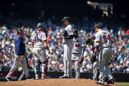 May 19, 2019; Seattle, WA, USA; Minnesota Twins starting pitcher Kyle Gibson (44) is visited on the mound by Minnesota Twins pitching coach Wes Johnson, left in the fifth inning against the Seattle Mariners at T-Mobile Park. Mandatory Credit: Lindsey Wasson-USA TODAY Sports