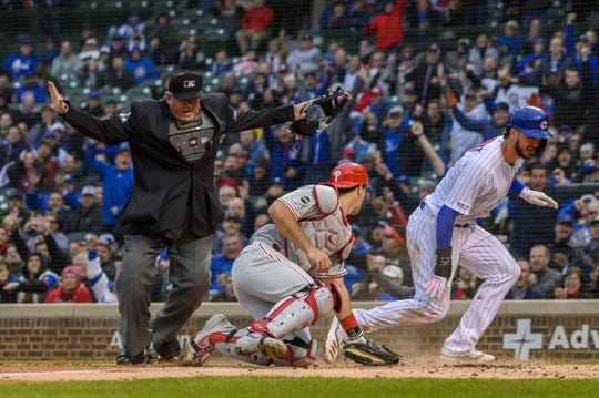 May 21, 2019; Chicago, IL, USA; Chicago Cubs third baseman Kris Bryant (17) slides safely into home plate to score against Philadelphia Phillies catcher J.T. Realmuto (10) as home plate umpire Hunter Wendelstedt (21) signals the call during the first inning at Wrigley Field. Mandatory Credit: Patrick Gorski-USA TODAY Sports