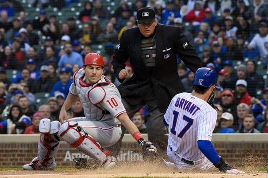 May 21, 2019; Chicago, IL, USA; Chicago Cubs third baseman Kris Bryant (17) slides safely into home plate to score against Philadelphia Phillies catcher J.T. Realmuto (10) during the first inning at Wrigley Field. Mandatory Credit: Patrick Gorski-USA TODAY Sports