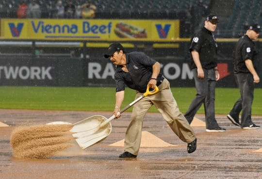 May 27, 2019; Chicago, IL, USA; Jose Diaz puts infield conditioner on the field as Umpire's Chris Conroy (98) and Mark Carlson (6) look at the condition of the field during the fifth inning of a game between the Chicago White Sox and the Kansas City Royals at Guaranteed Rate Field. Mandatory Credit: David Banks-USA TODAY Sports